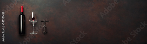 Fotografie, Obraz Bottle of wine with wineglass and corkscrew on rusty brown background