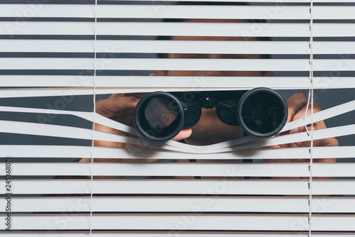 Canvastavla suspicious young man with binoculars spying through blinds