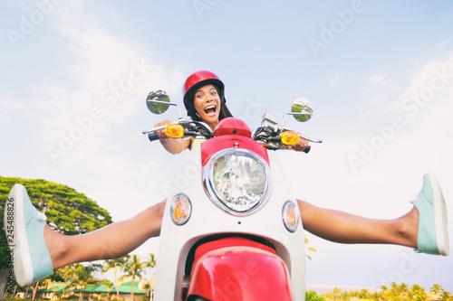 Fototapeta premium Zabawa w podróży, zabawny turysta, beztroska jazda skuterem na letnią podróż. Krzycząca Azjatycka dziewczyna wygłupia się z nogami na motocyklu.