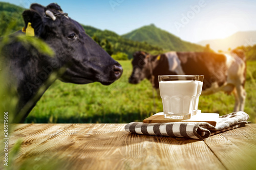 Carta da parati Fresh milk on wooden desk and spring landscape with cows and mountains