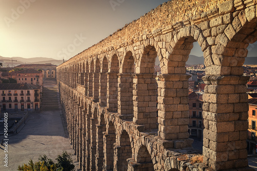 Fotografiet Perspective view of the roman aqueduct of the city of Segovia, next to some hous