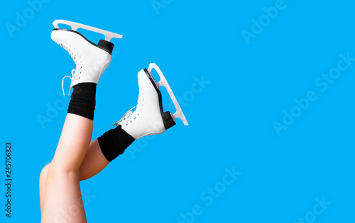 Ice skating, skater, female feet in skates shoes isolated on blue background. Winter time. Girl, winter sports, copy space, panoramic view