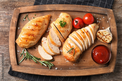 Wooden board with fried chicken breasts and sauce on table, top view