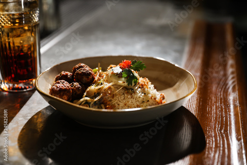 Plate with rice and meat balls served on table