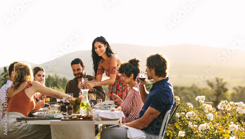 Photographie Woman serving food to friends at dinner party