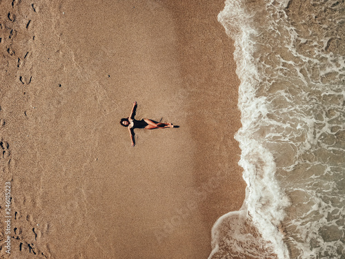 Obraz na plátně Aerial top view young woman lying on the sand beach and waves