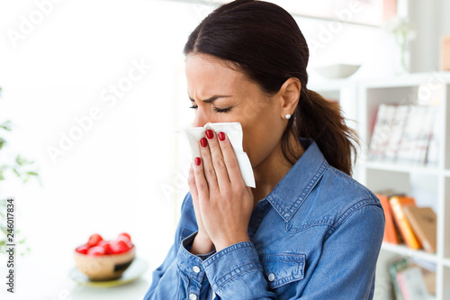 Canvas Print Unhealthy young woman sneezing in a tissue in the living room at home