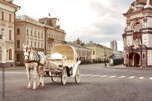 Fotomural Emoty white carriage with white horse waits for tourists in central square, Kaza