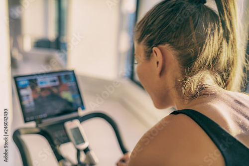 Smart fitness home workout biking screen with online classes woman training on stationary bike equipment indoors for biking exercise. Indoor cycling. Focus on the sweat on person's back.