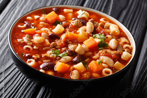Italian tomato faggioli soup with vegetables, ditalini pasta and ground beef close-up in a bowl on a wooden table. horizontal