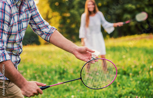 Couple playing badminton in the park. Sport, recreation, lifestyle, love concept