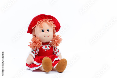 Soft doll in a red dress and hat on a white background Fototapet