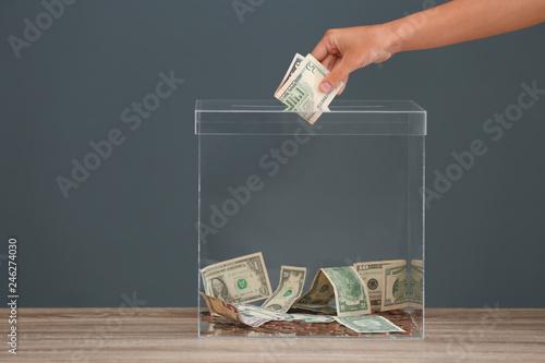 Slika na platnu Woman putting money into donation box on table against grey background, closeup