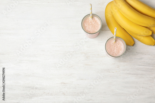 Healthy protein shake in glasses, bananas and space for text on white wooden background