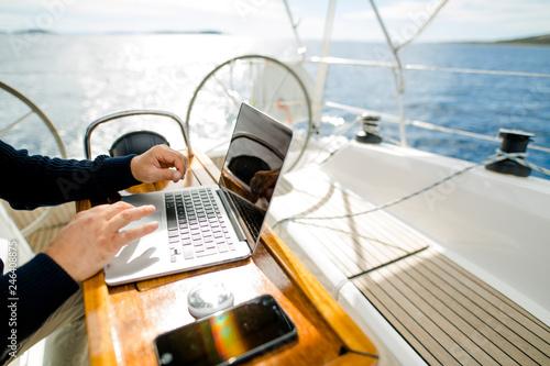 Obraz na plátně Digitaler Nomade mit Laptop arbeitet auf einem Segelboot