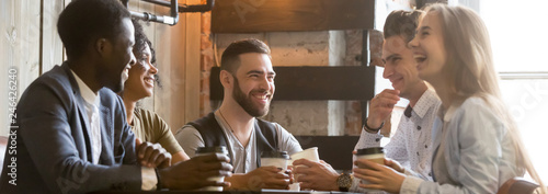 Horizontal photo happy millennial diverse friends sitting at cafe chatting having fun drink coffee enjoy time together. Multiracial friendship leisure activity concept banner for website header design
