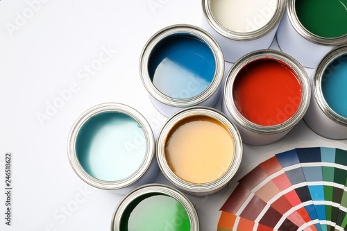 Paint cans and color palette on white background, top view
