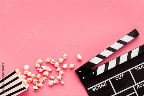 Film watching concept. Clapperboard and popcorn on pink background top view c...