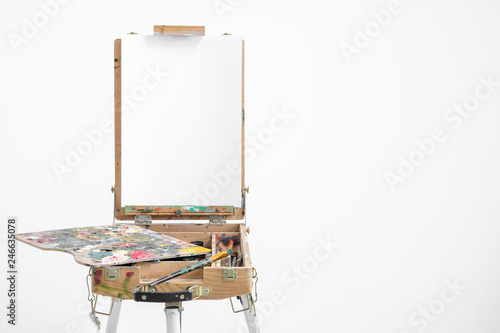Photo Artist easel with blank canvas on a white background.