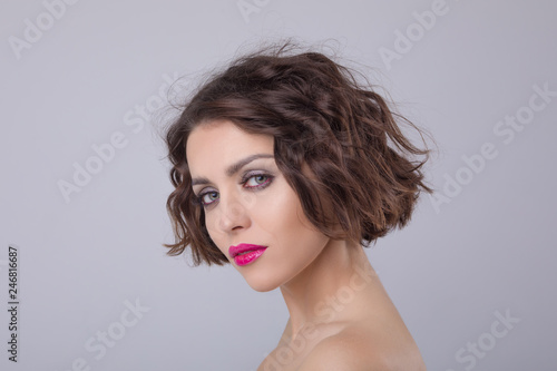 Portrait of a beautiful woman with short wavy hair and bright lips.