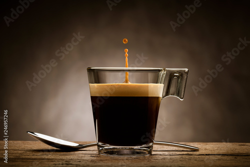 Black coffee in glass cup with teaspoon and jumping drop, on wooden table