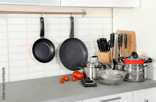 Set of clean cookware and utensils on table in modern kitchen