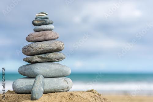 Leinwand Poster Steinturm an einem Strand als Hintergrund mit Textfreiraum