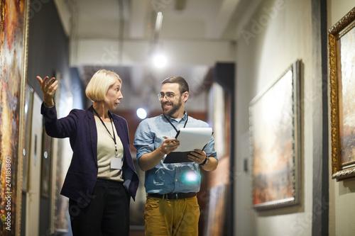 Fototapeta Portrait of two cheerful museum workers discussing paintings walking in art gall