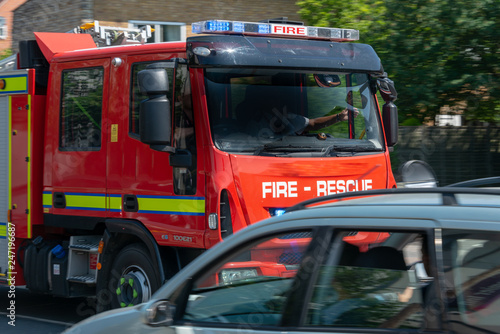 Fototapeta fire engine truck speeds along road to deal with emergency