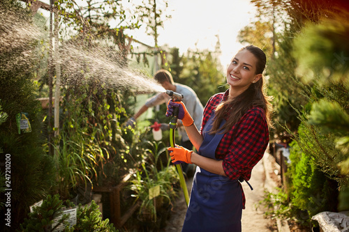 Canvas-taulu Smiling girl gardener sprays water plants in the beautiful nursery-garden on a sunny day