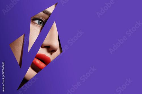Fotografia Plump bright red lips in violet paper frame