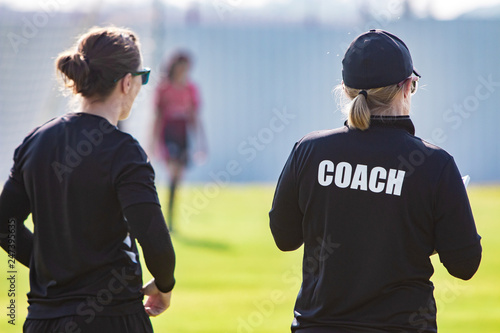 Photographie Back view of female sport coach and her assistant in black COACH shirt at an out