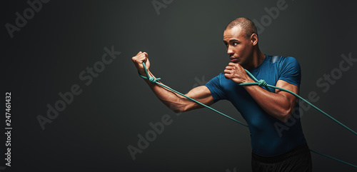 Fotografia Go! Sportsman working out with resistance band over dark background