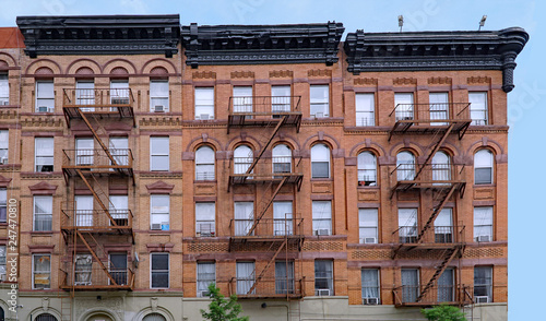 Photo old brown brick New York apartment building with external fire escape ladders