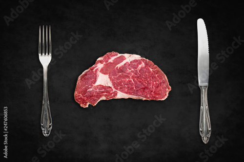 Fotografering raw steak / red meat with knife and fork on black background -