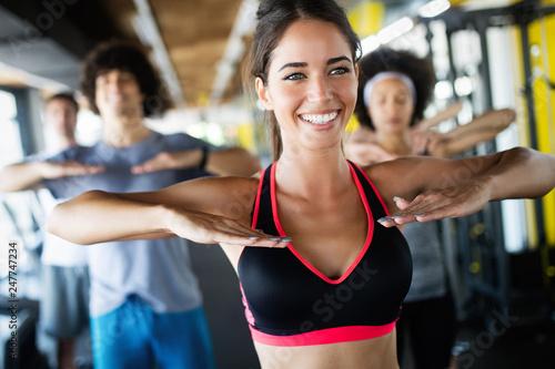 Grupa młodych ludzi robi ćwiczenia w siłowni