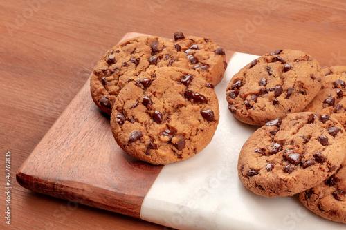 Obraz na plátně Freshly baked golden brown chocolate chip cookies on a dark rustic wooden backgr