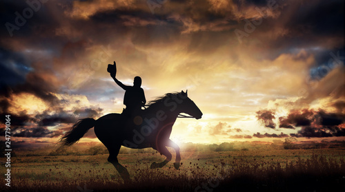 Fotografia A silhouette of a cowboy and horse at sunset