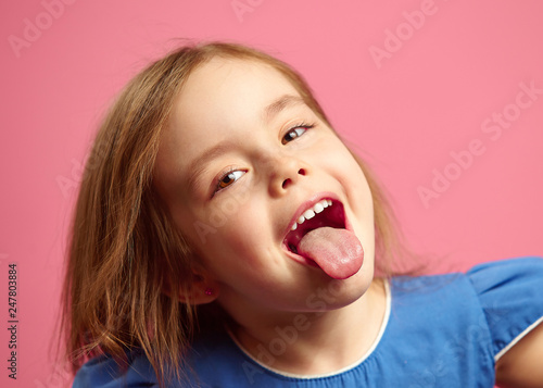 Wallpaper Mural Close up shot of little girl with her tongue out over pink isolated