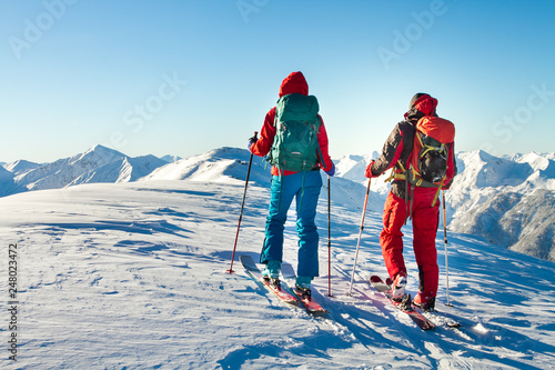 Canvas Print Man and woman ski tourer enjoying the view on a summit in the alps