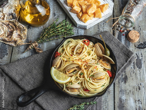 Tablou Canvas Pasta with seafood, shellfish clams in the iron pan portion, with lemon and seas