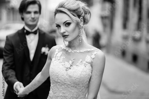 Obraz na plátně stylish bride and groom walking in city street