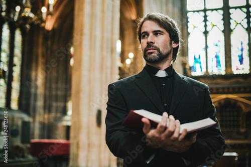 Fotografia Christian priest standing by the altar