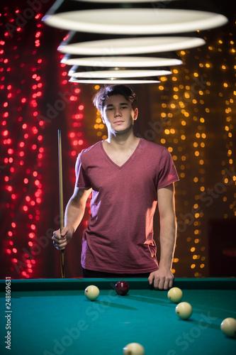Obraz na płótnie A young man standing in billiard club holding a cue