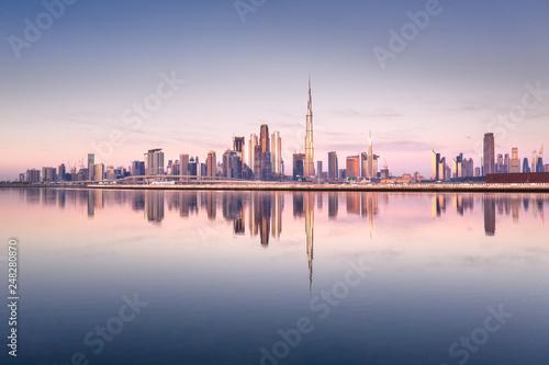 Fototapeta Beautiful colorful sunrise lighting up the skyline and the reflection of Dubai Downtown