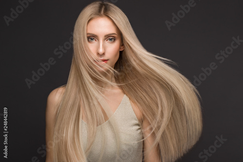 Tela Beautiful blond girl in move with a perfectly smooth hair, and classic make-up