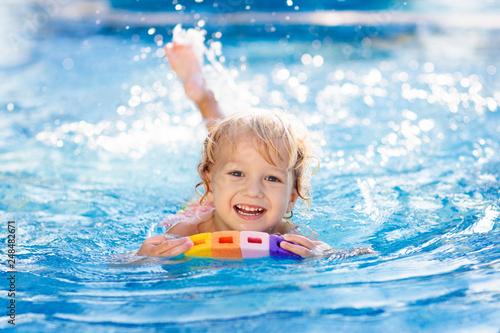 Wallpaper Mural Child learning to swim. Kids in swimming pool.
