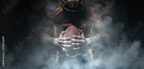 Canvas Print American football player on a dark background in smoke in black and orange equipment