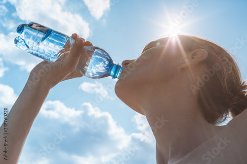 Tableau sur Toile Female drinking bottle of water on a hot summer day.