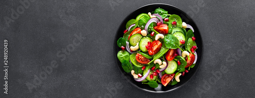 Canvas Print Spinach salad with fresh cucumbers, tomato, onion, pomegranate, sesame seeds and cashew nuts on black background